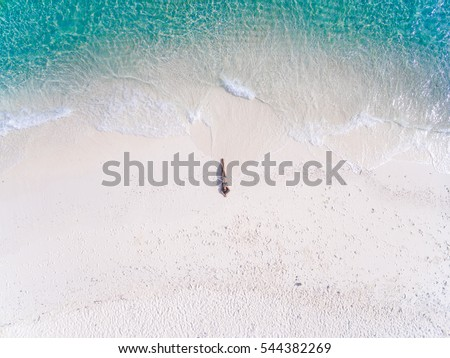 Young woman in a bikini lying on the back on the white sand near the waves of blue sea. Top view. Kai island, Andaman Sea, Phuket, Thailand. Aerial Shooting. #544382269