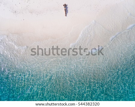 Young woman in a bikini lying on the back on the white sand near the waves of blue sea. Top view. Kai island, Andaman Sea, Phuket, Thailand. Aerial Shooting.