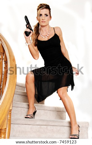 Young woman in a black cocktail dress and crystal necklace and bracelet sneaking down the stairs with a 45 caliber handgun