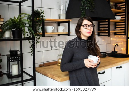 Young woman in a dark gray dress in the modern kitchen, the kitchen drinking tea. Good mood