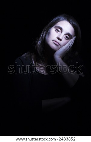 Young woman in a dark room with a das and melancholic expression in her face. Black background.