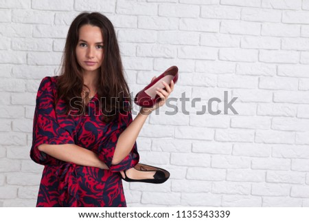 Young woman in a difficult moment to choose which shoe to wear. #1135343339