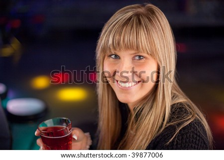 young woman in a discotheque is having a drink