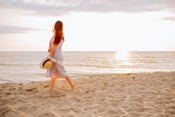 Young woman in a dress holding straw hat and walking alone on empty sand beach at sunset sea shoreand smiling. Single or divorsed girl.