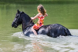 Young woman in a flowered dress with long red hair on a black horse leads a horse in the water. Happy woman on horse in river.