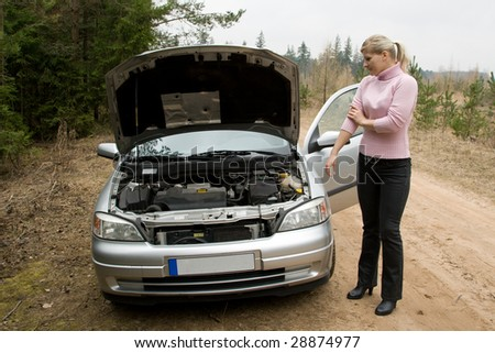 Young woman in a forest road with broken silver car.