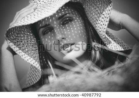 Young woman in a hat rural portrait. Black and white.