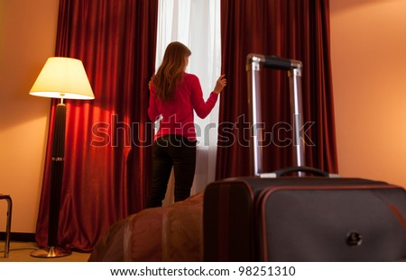 Young woman in a hotel opening window