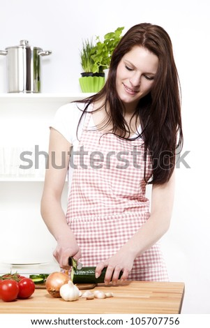 young woman in a kitchen cutting cucumber for salad