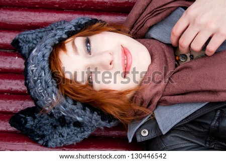 Young woman in a knitted hat lying on the bench