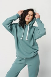 young woman in a posh stylish youth sports suit in a hoodie with a hood on a white background isolate