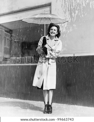 Young woman in a raincoat and umbrella standing in the rain