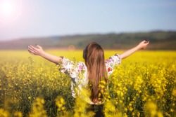 young woman in a rapeseed field. Young joyful girl wearing traditional romanian blouse. Low key, dark background, spot lighting, and rich Old Masters