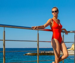 young woman in a red swimsuit on the sea pier against the background of the azure sea