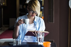 Young woman in a restaurant reading a book
