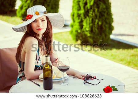 Young woman in a restaurant with elements of paste on hat