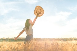 Young woman in a ripe wheat field celebrating with a hat in hand in a sunny wheat field. Concept of prosperity and warmth.
