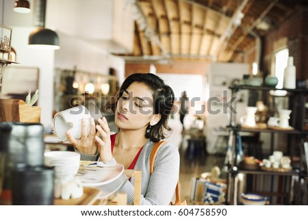 Young woman in a shop, looking at a ceramic jug