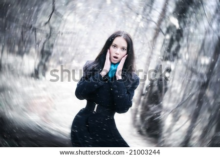 Young woman in a snowstorm. Background blur effect.