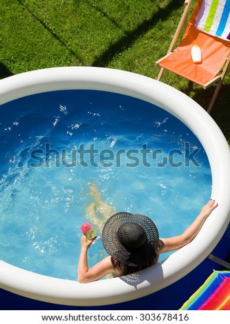 Young woman in a straw hat relaxing in the garden pool.