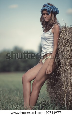 Young woman in a summer field. Calm pensive mood.