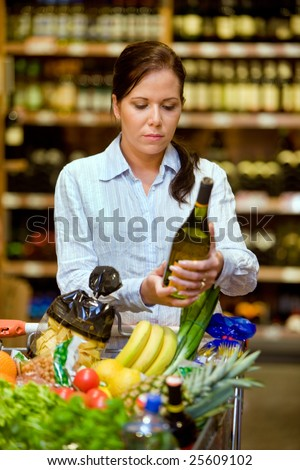 Young woman in a supermarket to buy wine