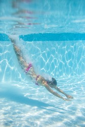 Young woman in a swimming pool performing some synchronized swimming drills