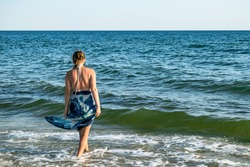 Young woman in a swimsuit and pareo walks into the sea - view from the back. Real adult girl on a background of blue water with waves. Background with copy space