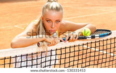 Young woman in a tennis dress and with the racket in her hand leaning on the net