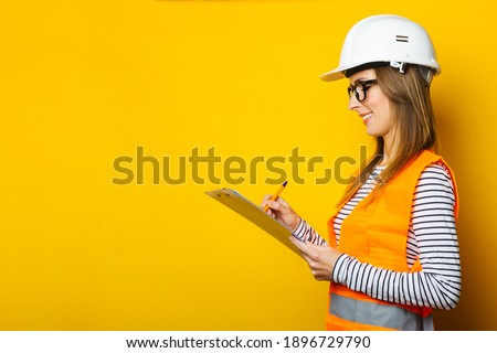 Young woman in a vest and hard hat holds a clipboard and takes notes on a yellow background. Concept for construction, new building, renovation. Banner. Photo stock ©