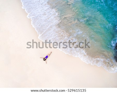 Young woman in a violet bikini lying on the back on the sand near the waves of blue sea. Top view. Surin beach, Andaman Sea, Phuket, Thailand. Aerial Shooting.