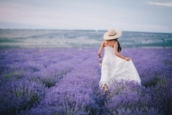 Young woman in a white dress and straw hat running in a lavender field with basket