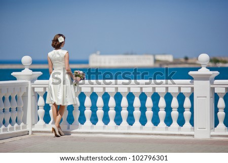 Young woman in a white dress looks at the sea