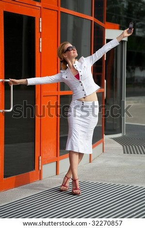 Young woman in a white suit pulls her hand with mobile phone up