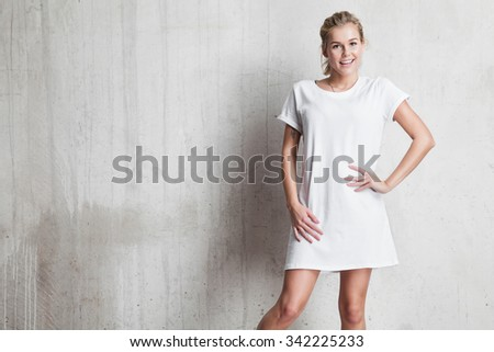 Young woman  in a white T-shirt against a background of a cement wall Photo stock ©