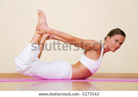 Young woman in a yoga position (Dhanurasana)