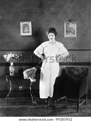 Young woman in an apron and a duster standing in a living room