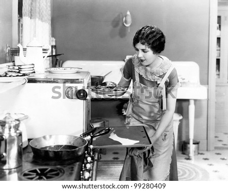 Young woman in an apron in her kitchen taking food out of the oven