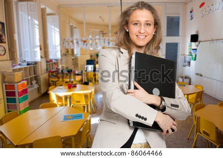 Young woman  in an elementary school classroom holding a laptop