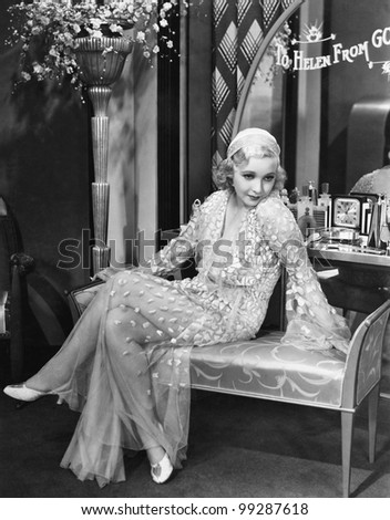 Young woman in an evening gown sitting on an upholstered bench