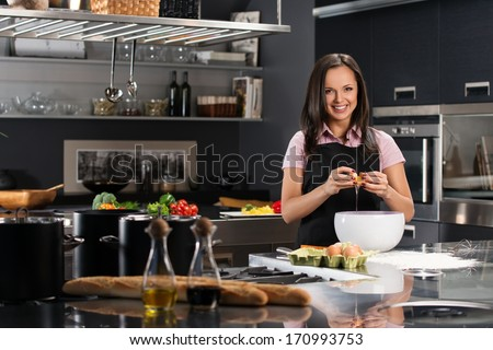 Young woman in apron breaking eggs for a dough on a modern kitchen #170993753