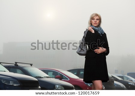 Young woman in autumn foggy morning against a car parking