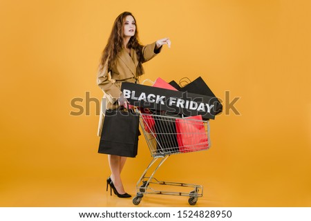 young woman in autumn trench coat with black friday sign and colorful shopping bags in pushcart isolated over yellow