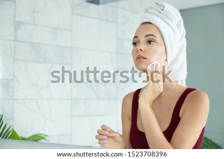 Young woman in bath towel on head apply cleansing tonic with cotton pads. Girl remove makeup with micellar water. Face cleanser. Pure healthy skin. Morning facial treat. Mirror reflection at bathroom
