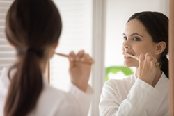 Young woman in bathrobe brushing teeth with wooden bamboo toothbrush. Teen girl choosing eco friendly tools for morning bath routine, oral mouth hygiene, protection from caries. Mirror reflection