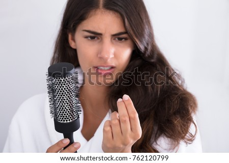 Young Woman In Bathrobe Holding Comb Looking At Hair Loss At Home