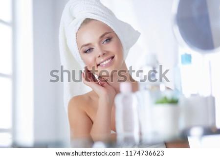Young woman in bathrobe looking in bathroom mirror #1174736623