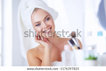 Young woman in bathrobe looking in bathroom mirror #1176397825