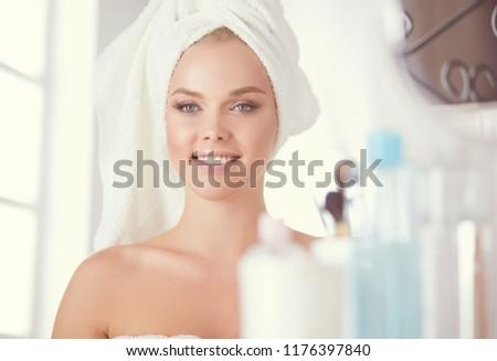 Young woman in bathrobe looking in bathroom mirror #1176397840