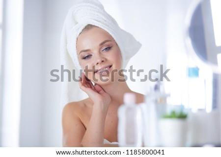 Young woman in bathrobe looking in bathroom mirror #1185800041